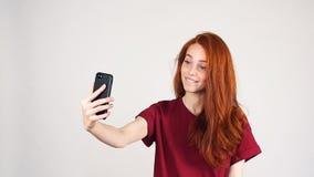 Den roliga modeflickan gör selfie på vit bakgrund, ultrarapid arkivfilmer