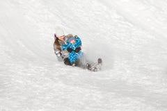 Den roliga modern och sonen glider ner en snökulle på en solig dag för vinter` s Arkivfoto