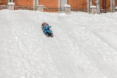 Den roliga modern och sonen glider ner en snökulle på en solig dag för vinter` s Arkivfoton