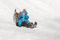 Den roliga modern och sonen glider ner en snökulle på en solig dag för vinter` s Royaltyfri Fotografi