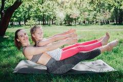 Den roliga och lyckliga flickan håller jämvikt och ser till kameran De lyckliga ler och blickar Yoga och pilates Royaltyfria Foton