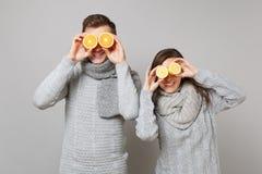 Den roliga parflickagrabben i gråa tröjor, scarves rymmer tillsammans den orange citronen isolerad på grå väggbakgrundsstudio arkivfoton