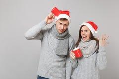 Den roliga parflickagrabben i scarves för tröjor för den röda Santa Christmas hatten gråa rymmer kopp te isolerade på grå väggbak royaltyfria foton