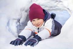 Den roliga pojken i vinter beklär att spela på en snögrotta Fotografering för Bildbyråer