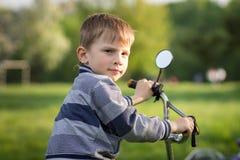 Den roliga pojken med cykeln som har gyckel i sommar, parkerar Arkivfoto