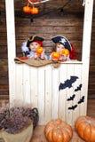 Den roliga pojken och flickan piratkopierar in dräkter i studion med landskap för allhelgonaafton Arkivbilder
