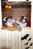 Den roliga pojken och flickan piratkopierar in dräkter i studion med landskap för allhelgonaafton Royaltyfri Foto