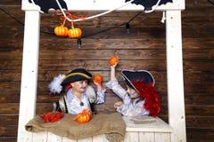 Den roliga pojken och flickan piratkopierar in dräkter i studion med landskap för allhelgonaafton Arkivbild