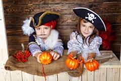 Den roliga pojken och flickan piratkopierar in dräkter i studion med landskap för allhelgonaafton Royaltyfri Fotografi