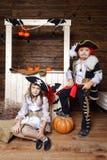 Den roliga pojken och flickan piratkopierar in dräkter i studion med landskap för allhelgonaafton Royaltyfria Bilder