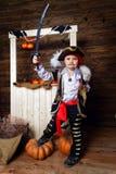Den roliga pojken piratkopierar in dräkten i studion med landskap för allhelgonaafton Arkivbild
