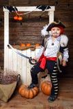 Den roliga pojken piratkopierar in dräkten i studion med landskap för allhelgonaafton Royaltyfri Fotografi