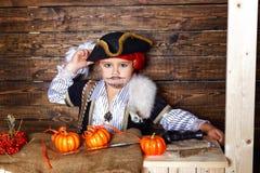 Den roliga pojken piratkopierar in dräkten i studion med landskap för allhelgonaafton Arkivfoto