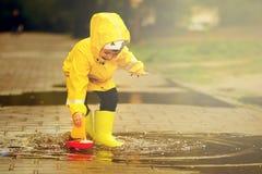 Den roliga pojken ska spara dess plast- fartyg som sjönk i en pöl en pojke i en gul regnrock går i parkerar fotografering för bildbyråer