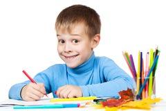Den roliga pojken tecknar med blyertspennor royaltyfri foto