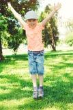 Den roliga pysen hoppar utomhus Lyckligt och sunt barndombegrepp Den gulliga pojken som spelar i sommar, parkerar Det lyckliga ba royaltyfri fotografi