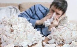 Den roliga sjuka mannen, som har influensa eller förkylning, blåser hans näsa Royaltyfri Foto