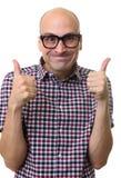 Den roliga skalliga mannen gör en gest upp tummar Arkivfoto