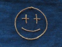 Den roliga smileyen av tvinnar i grov bomullstvill Handgjord symbol för Emoji tecken Arkivbilder