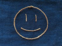 Den roliga smileyen av tvinnar i grov bomullstvill Handgjord symbol för Emoji tecken Arkivfoton