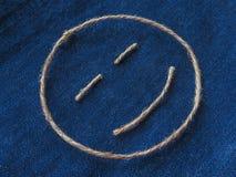Den roliga smileyen av tvinnar i grov bomullstvill Handgjord symbol för Emoji tecken Royaltyfria Bilder