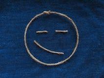 Den roliga smileyen av tvinnar i grov bomullstvill Handgjord symbol för Emoji tecken Arkivfoto