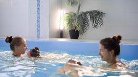 Den roliga ståenden av barnet lär simning, dykning i blåttpöl med gyckel - att hoppa djupt ner undervattens- med färgstänk stock video
