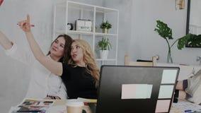 Den roliga ståenden av två nätta kvinnliga 30-talvänner har gyckel och kopplar av i arbetsplatsen Brunettkvinnan gör på selfie stock video