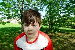 Den roliga tonåringpojken ser in i kamera i sommar parkerar Arkivbild