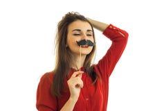 Den roliga unga flickan i röda ställningar för en blus med stängda ögon och uppehällen skyler över brister mustaschen nära munnen Arkivfoton