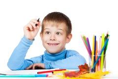Den roliga ungen tecknar med blyertspennor royaltyfria foton