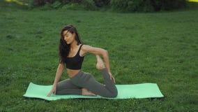 Den roliga videoen om den unga kvinnan som gör yogaövning och omkring bedrar i, parkerar utomhus på morgonen lager videofilmer