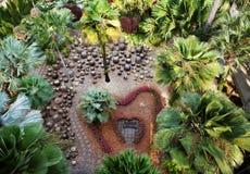 Den romantiska bänken för ett förälskelsepar i mitt av en hjärta formade blomsterrabatten arkivfoton