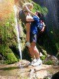 Den romantiska bilden, man lyftte upp kvinnan bredvid skogvattenfallet Royaltyfria Bilder