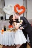 Den romantiska den kyssbruden och brudgummen i bröllop ge en bankett för Arkivfoto