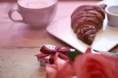 Den romantiska frukosten för dag för valentin` s firar Den närvarande asken, steg blommor, nytt giffelkaffe på trätabellen Fokus  Royaltyfri Bild