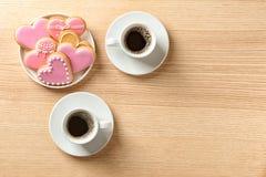 Den romantiska frukosten med hjärta formade kakor och koppar kaffe på trätabellen, bästa sikt fotografering för bildbyråer