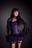 Den romantiska häxan i lilor och den svarta gotiska allhelgonaaftonen utrustar Royaltyfri Fotografi