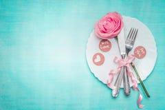 Den romantiska inställningen för stället för matställetabellen med rosa och undertecknar garnering på blå bakgrund, bästa sikt arkivfoton