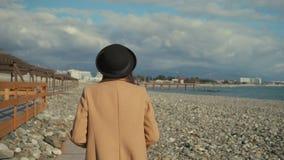Den romantiska kvinnan går på kiselstenkust i den soliga höstdagen, tillbaka sikt arkivfilmer
