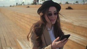 Den romantiska lyckliga flickan läser sms i hennes smartphone, sitter utomhus i solig dag lager videofilmer