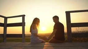 Den romantiska mannen och kvinnan sammanfogar händer i en hjärtaform mot solen Förälskelse och affektion stock video