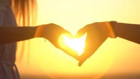 Den romantiska mannen och kvinnan sammanfogar händer i en hjärtaform mot solen Förälskelse och affektion lager videofilmer