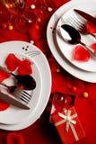 Den romantiska matställen bordlägger och vigselringar Arkivfoto