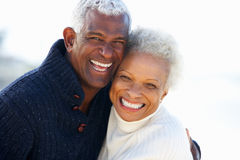 Den romantiska pensionären kopplar ihop att krama på strand Royaltyfria Bilder