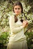 Den romantiska ståenden av flickan i de blommande körsbärsröda träden royaltyfria bilder