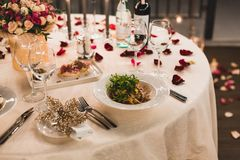 Den romantiska tabellinställningen med vin, härliga blommor i ask, tomma exponeringsglas, steg kronblad och stearinljus arkivbilder