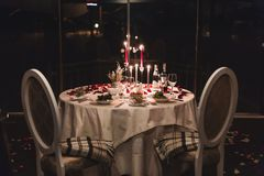 Den romantiska tabellinställningen med vin, härliga blommor i ask, tomma exponeringsglas, steg kronblad och stearinljus royaltyfri fotografi