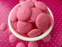 Den rosa chokladgodisen smälter på rosa prickbakgrund Arkivfoton