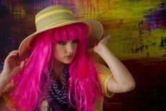 Den rosa haired flickan justerar hennes hatt, som hon ser av kamera till rätten. Arkivfoto